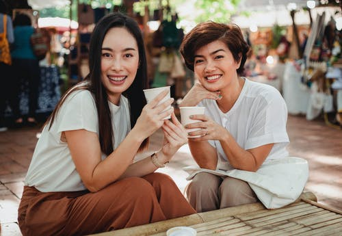 Pretty Asian women with takeaway coffees sitting in outdoor cafe