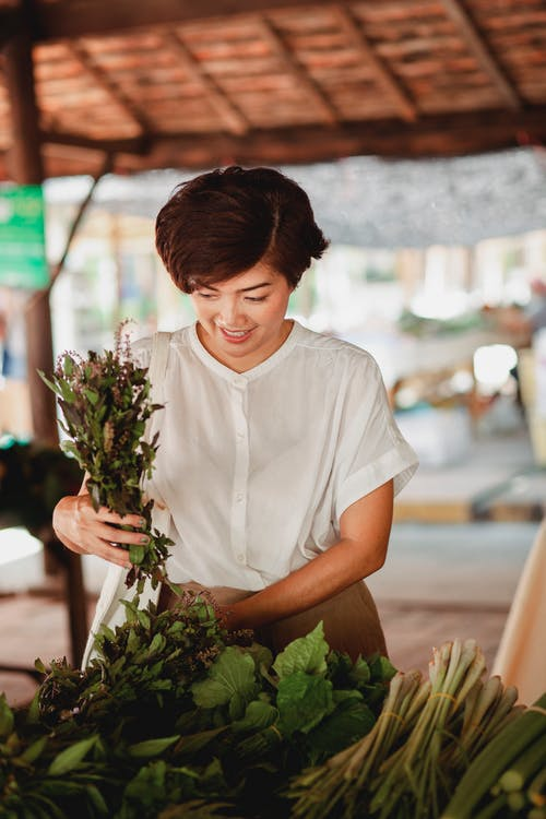 Cheerful Asian woman choosing fresh herbs at market