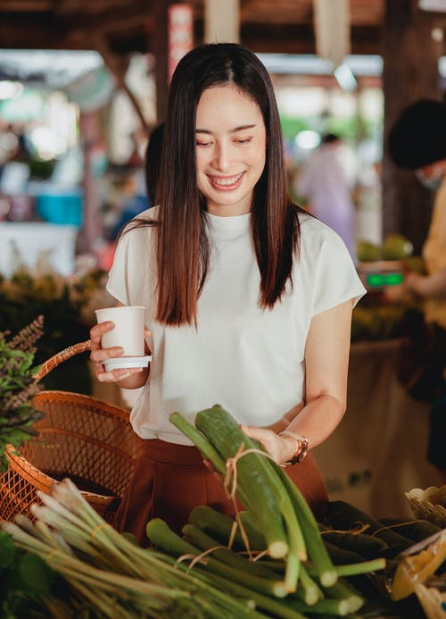 Positive Asian female shopper smiling while holding ripe lemongrass at oriental market with vegetables