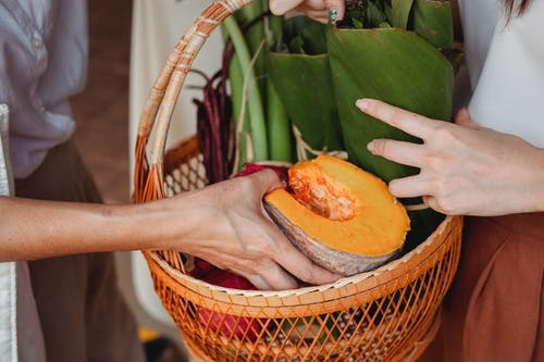 Side view of crop anonymous females putting pumpkin into wicker basket with vegetables