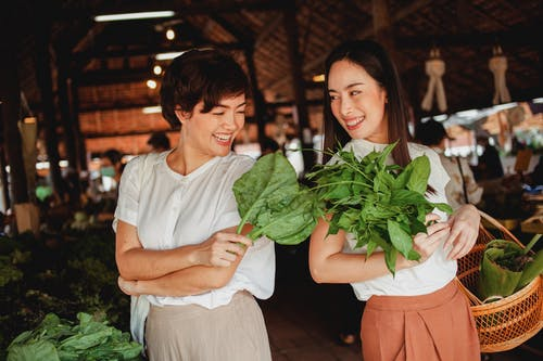 Glad Asian buyers with fresh green herbs in bazaar