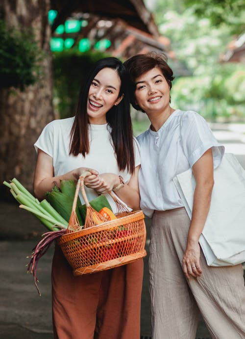 Happy Asian girlfriends with basket of vegetables in town