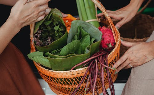 Crop women showing basket with green vegetables and herbs