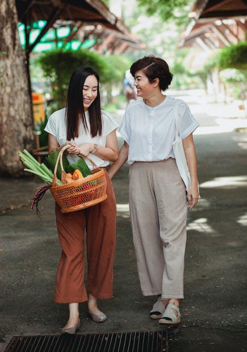 Happy Asian lesbian couple walking on city pavement
