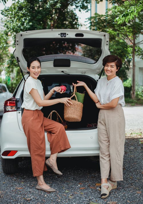 Positive Asian girlfriends with food basket near auto