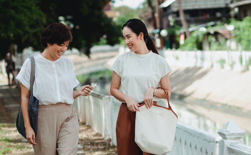 Happy Asian girlfriends talking while walking on street