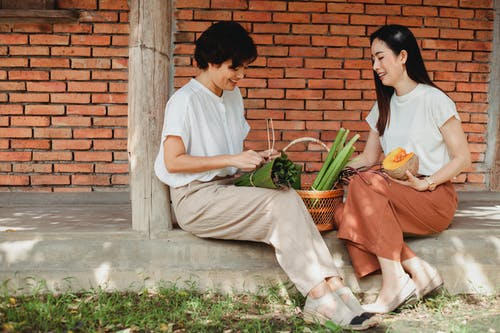 Cheerful Asian girlfriends tying bundle of fresh herbs on pavement