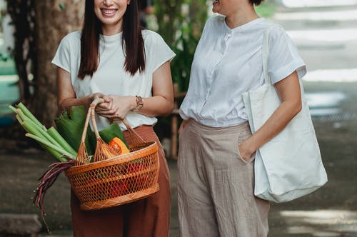 Crop positive girlfriends with food basket in city
