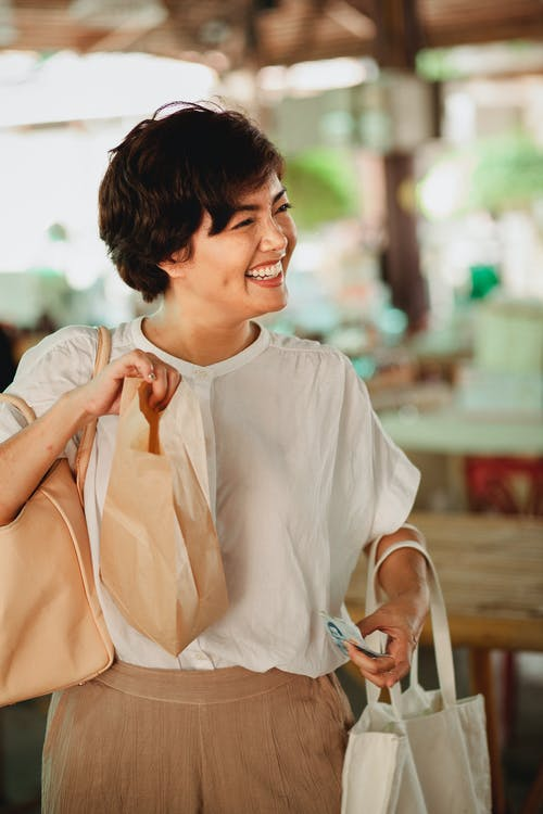 Positive Asian woman with food bag in market