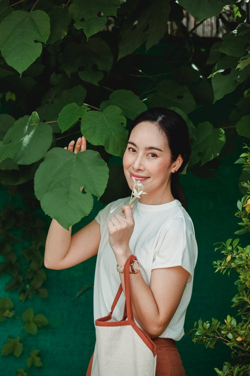 Smiling Asian woman with flower near tree