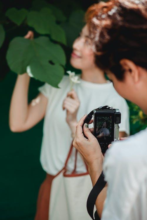 Crop woman taking photo of smiling Asian girlfriend on camera