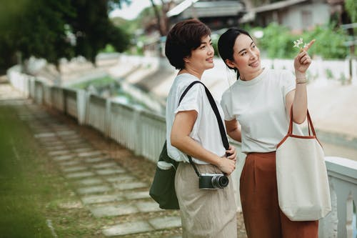 Young glad ethnic lady pointing with finger near girlfriend with photo camera while looking up on embankment