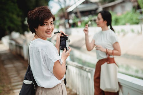 Smiling Asian woman taking photo of friend on camera