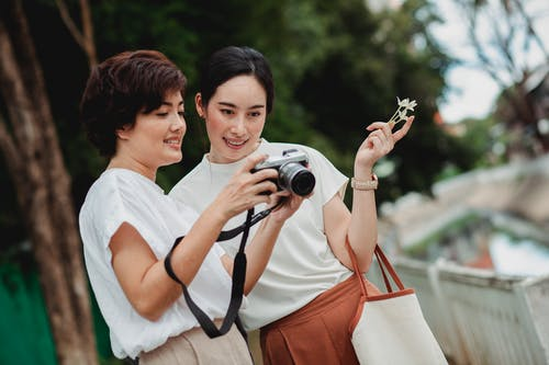 Young glad ethnic lady sharing photo camera with charming female partner on city street in summer