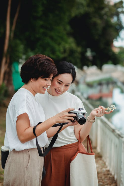 Smiling ethnic woman demonstrating photo on camera to best friend