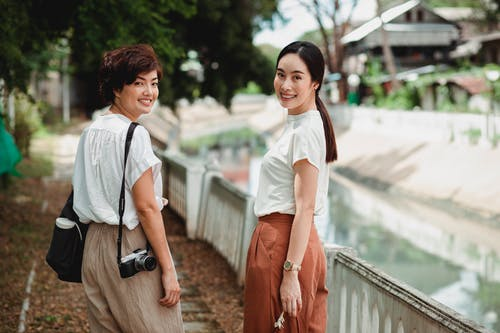 Happy Asian women on urban embankment near canal
