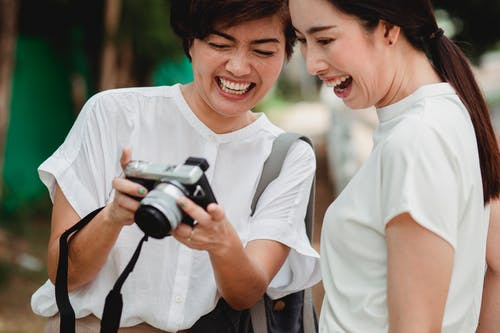 Crop smiling ethnic lady sharing digital photo camera with best friend in summer town