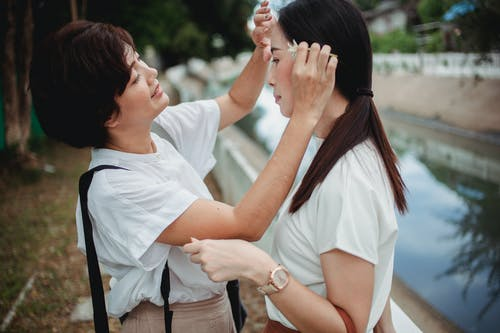 Smiling Asian woman touching forehead of homosexual partner on embankment
