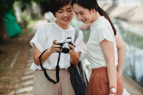 Crop ethnic woman sharing photo camera with smiling best friend