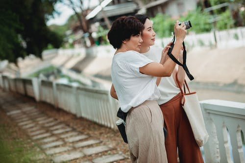 Young ethnic girlfriends in casual apparel taking photo on professional photo camera while standing on urban embankment