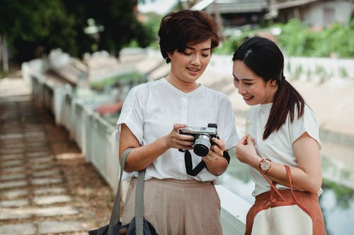 Asian woman sharing photo camera with cheerful best friend