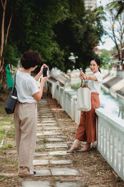 Anonymous woman taking photo of ethnic girlfriend on camera
