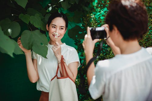 Unrecognizable woman taking photo of charming ethnic girlfriend on camera
