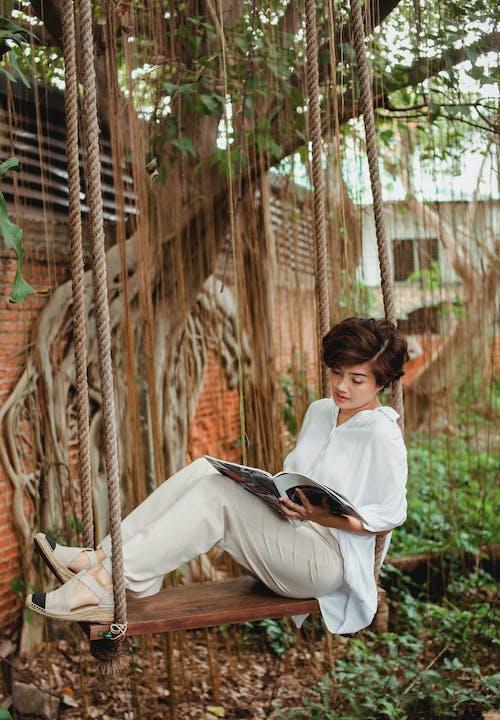 坦然的女人,在木制的秋千上休息