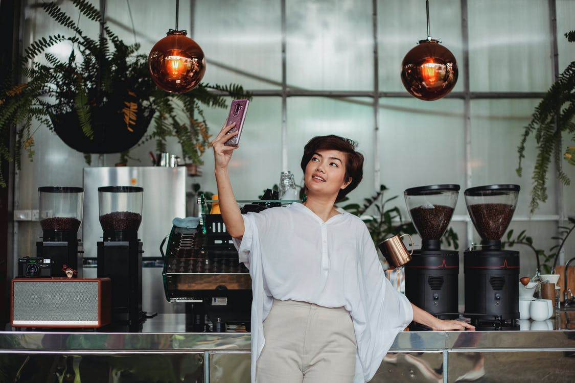 Cheerful Asian female with short brown hair in casual clothes standing against coffee machine and taking selfie on smartphone