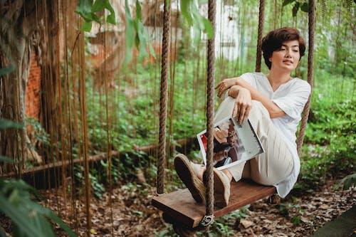 Pensive Asian female swinging on wooden swing