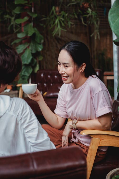 Smiling Asian female resting with friend in cafe