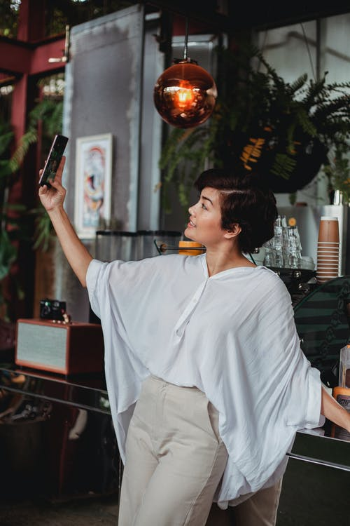 Side view of positive Asian female in stylish clothes raising hand and taking selfie on smartphone in cozy cafe