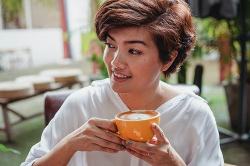 Cheerful Asian female with short brown hair in white blouse drinking cup of aromatic latte and looking away