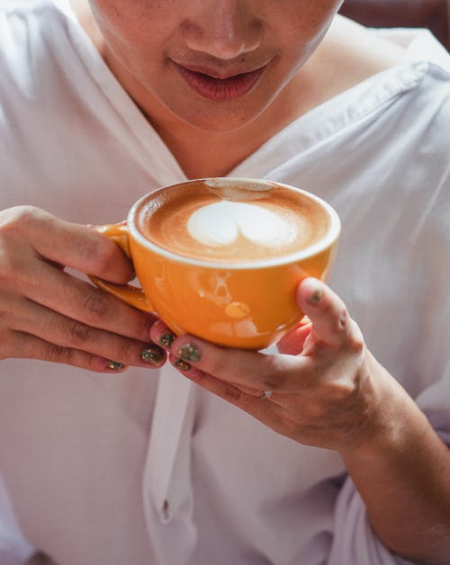 Female raising hands with cup of hot coffee
