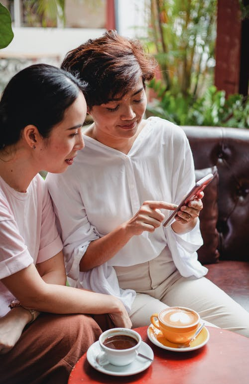 Calm Asian women looking at screen of smartphone