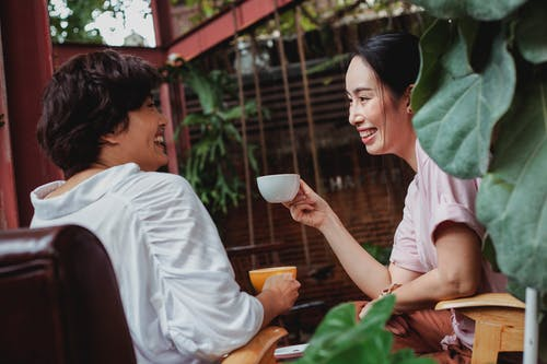 Happy Asian friends sitting with cups of hot beverage and laughing in cozy cafe in daytime