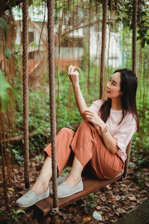 Cheerful Asian female resting on swings in garden