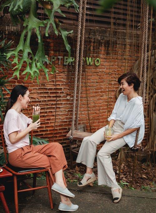 Happy Asian friends resting on terrace