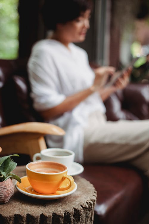 Ceramic cups of beverage placed on decorative wooden table against calm woman sitting on leather couch and using smartphone in cozy cafe in daylight