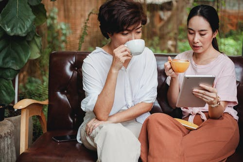 Thoughtful Asian women in casual clothes drinking cups of beverage and looking at screen of tablet