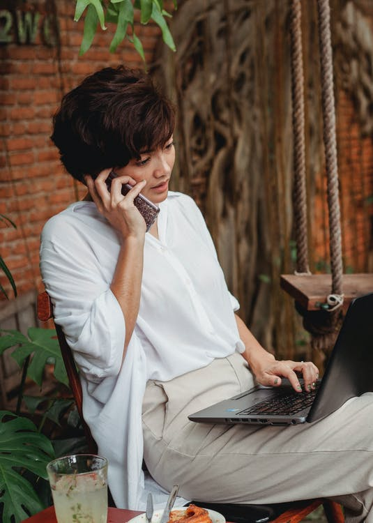 Pensive Asian female using laptop and talking on smartphone