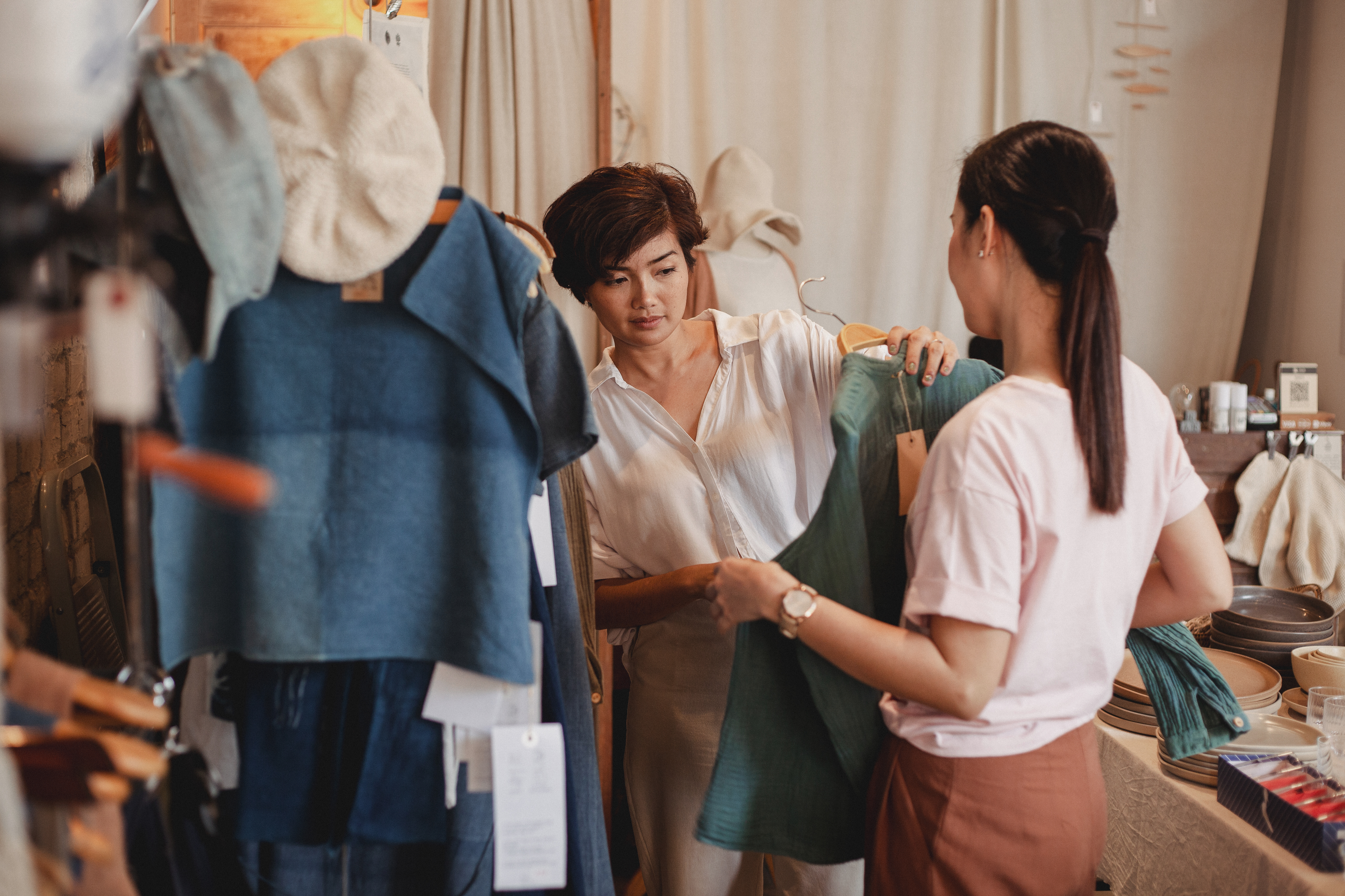unrecognizable shopper with asian girlfriend choosing clothes in shop