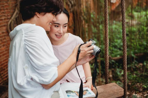 Crop cheerful Asian woman sharing photo camera with best friend
