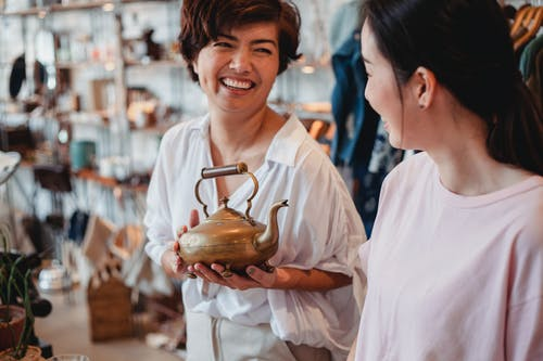 Crop cheerful ethnic female shoppers with oriental kettle speaking in local shop while spending time together and looking at each other