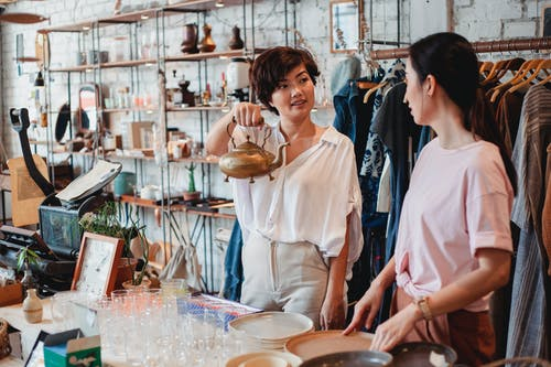 Young ethnic female shopper demonstrating metal kettle to partner while interacting near table with dishware in store and looking at each other