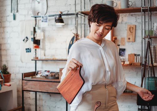 Young content ethnic female shopper with wooden cutting board in store with brick wall