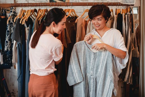 Glad Asian shoppers choosing apparel in clothing store