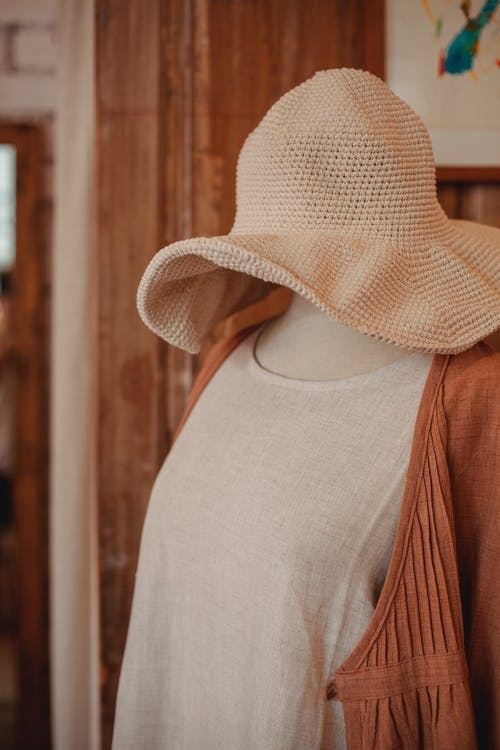 Plastic dummy with linen apparel and wavy panama hat in clothing store in daylight