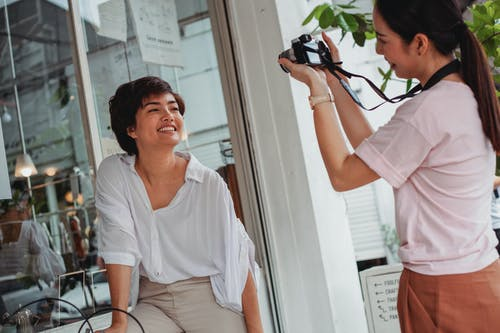 Crop Asian lady in casual wear taking photo of charming best friend on camera near glass wall in city