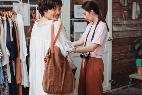 Crop young glad ethnic shopper with fabric bag near female partner choosing clothes in street shop